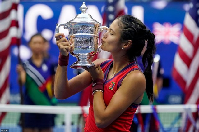 Raducanu plants a kiss on the trophy after cruising through the US Open without losing a single set