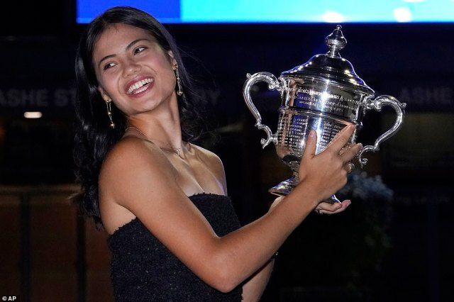 Emma Raducanu poses outside Arthur Ashe Stadium with the championship trophy after she defeated Leylah Fernandez in the women's singles final of the US Open tennis championships