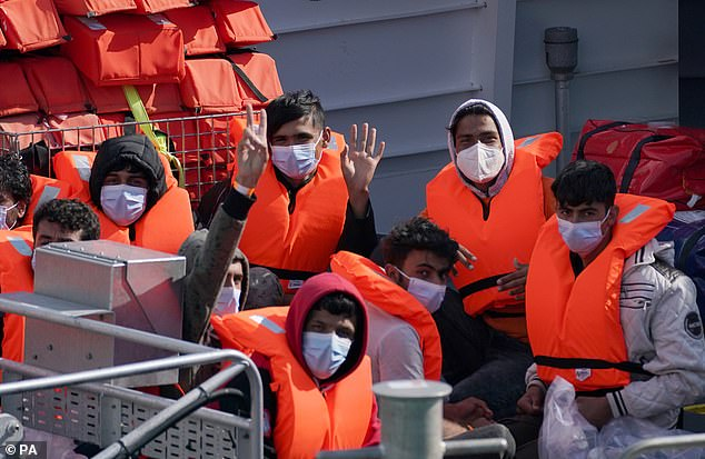 Record-breaking numbers of migrants have so far made it across the Channel this year - with numbers already nearing double those recorded in the whole of 2020. Above: Masked suspected migrants wave at Dover, Kent