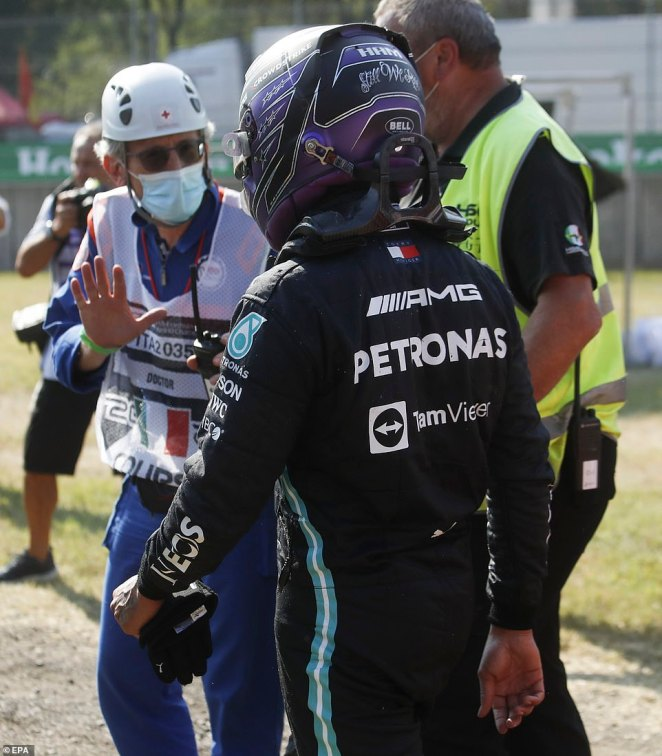 A race marshall checks on the condition of Hamilton after he emerged from his Mercedes to walk back to the pit lane