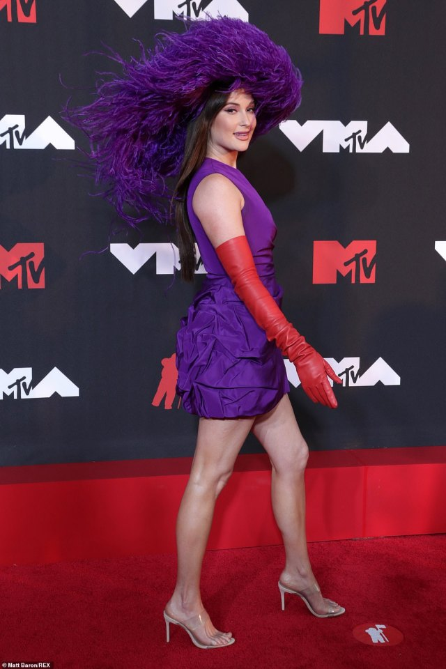 Charmer: Kacey Musgraves put a groovy twist on Southern Belle style wearing a fabulous feathered hat with a silk Valentino party dress and red leather opera gloves