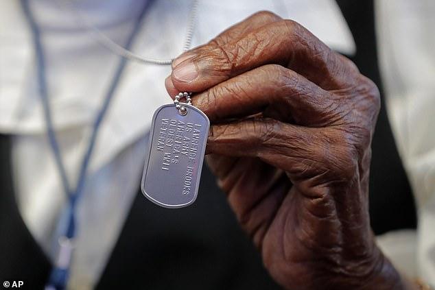 World War II veteran Lawrence Brooks holds a dog tag honoring him as the oldest living World War II veteran