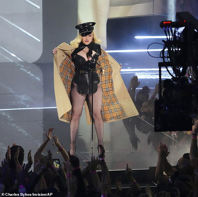 Stripping down: She was seen opening her Burberry trench coat to reveal and erotica-inspired outfit