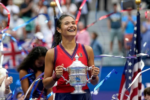 Emma Raducanu holds the US Open championship trophy after defeating Leylah Fernandez in the singles final on Saturday