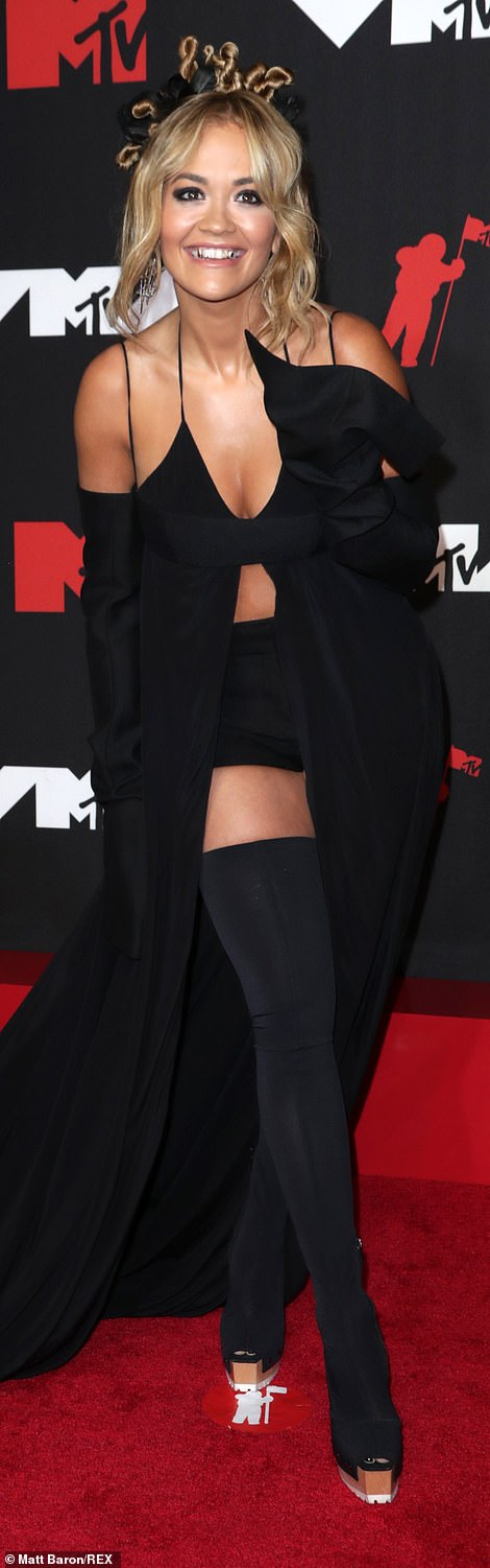 Daring:The R.I.P hitmaker also sported a pair of black shorts while she added height to her frame with daring thigh-high platform boots