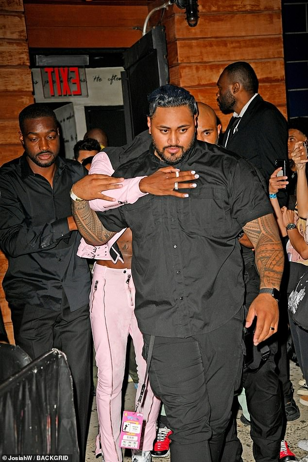 Holding on: The rapper held on to a tattooed bodyguard dressed in all black