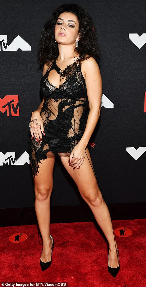 Not holdng back: Charli, real name Charlotte Emma Aitchison, pulled out all the stops for the evening's look as she sported a tattered mesh mini over her lingerie