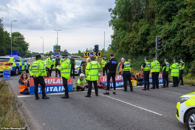 Police stand next to the Insulate Britain protesters at junction 20 of the M25 at Kings Langley in Hertfordshire this morning