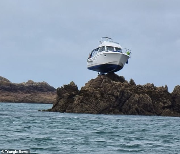 The motor cruiser became stranded on top of a rock 10ft in the air after colliding with an underwater reef