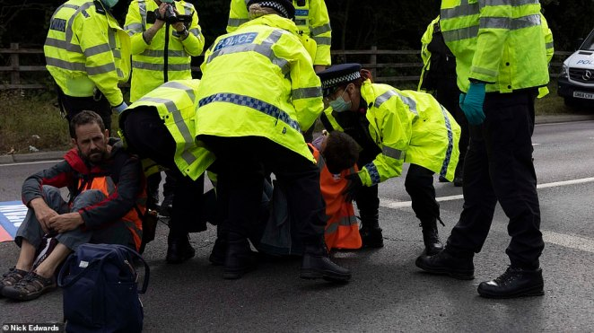 Police officers remove a protester who stopped traffic at junction three of the M25 at Swanley in Kent yesterday morning