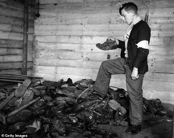 A young man examines a pile of boots, shoes and clogs at the concentration camp in 1944