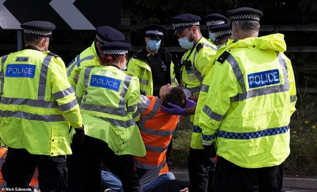 Police and protestors at junction 3 of the M25 this morning after the activists stopped traffic at Swanley in Kent