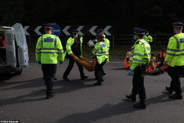 Protesters are taken away by police after the Insulate Britain group caused chaos at the M25 in Swanley, Kent, today