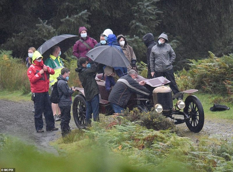 Pouring:A flurry of crew members gathered around the namesake character with umbrellas in-hand as the heavens began to open over the hilly countryside spot
