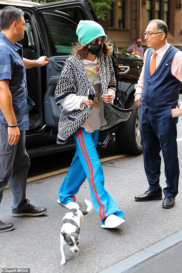 Shabby-chic:Cara Delevingne, 29, nailed shabby-chic when she stepped out with her beloved pet dog Alfie in New York on Monday wearing white slippers