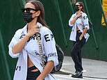 Irina Shayk teases her taut midriff in a partially unbuttoned shirt as she steps out in New York
