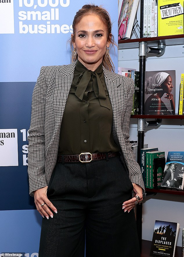 Biz look 101:Jennifer Lopez adopted a business look this weekend with a sharp blazer over a bow tie blouse and over-the-knee skirt with her hair back