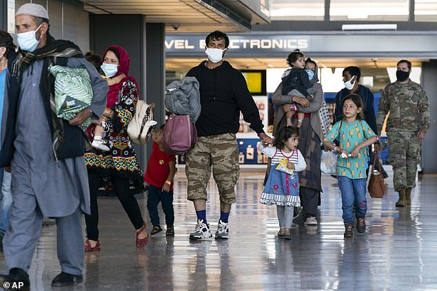 Families evacuated from Kabul walk through the terminal before boarding a bus after they arrived at Washington Dulles International Airport in Virginia last week