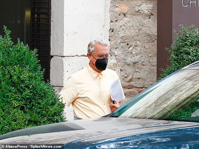 Hard at work:The acting professional seemed to be running his lines en route to the filming location, as he carried a script into the car