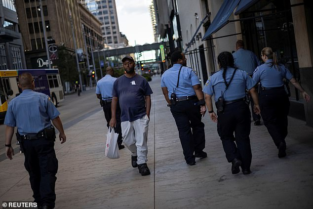 A man walks by a group of police officers in downtown Minneapolis last week. The department has lost nearly a quarter of its officers and can't find recruits willing to take the job