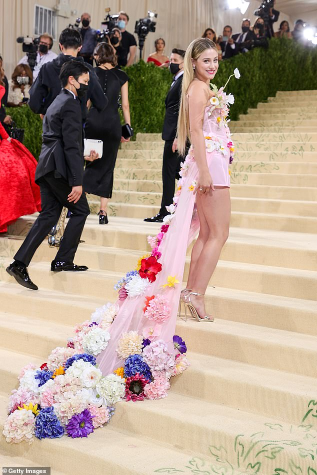 Stunning:The 25-year-old actress slipped her trim figure into a pink voile gown covered in various flowers from the bodice to the train