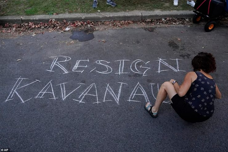 A protestor writes 'resign Kavanaugh' in chalk outside the Justice's home on Monday