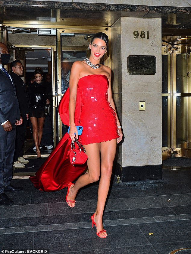 Red hot: Kim's younger sister Kendall looked red hot in a micro mini dress with a large bow in the back with a train flowing from it