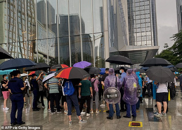 Protesters have mobbed a failing Chinese property company with $300billion of debt to demand their money back amid fears it could collapse