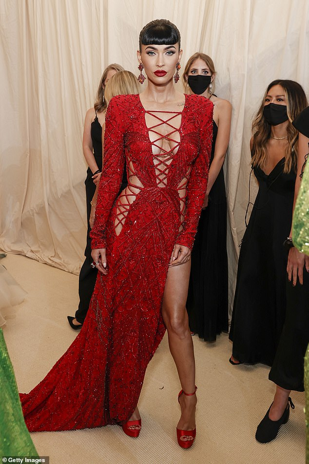 Turning heads:Earlier in the night she wowed in a long cut-out red gown as she put on a typically sizzling red carpet display and showed off her new fringe