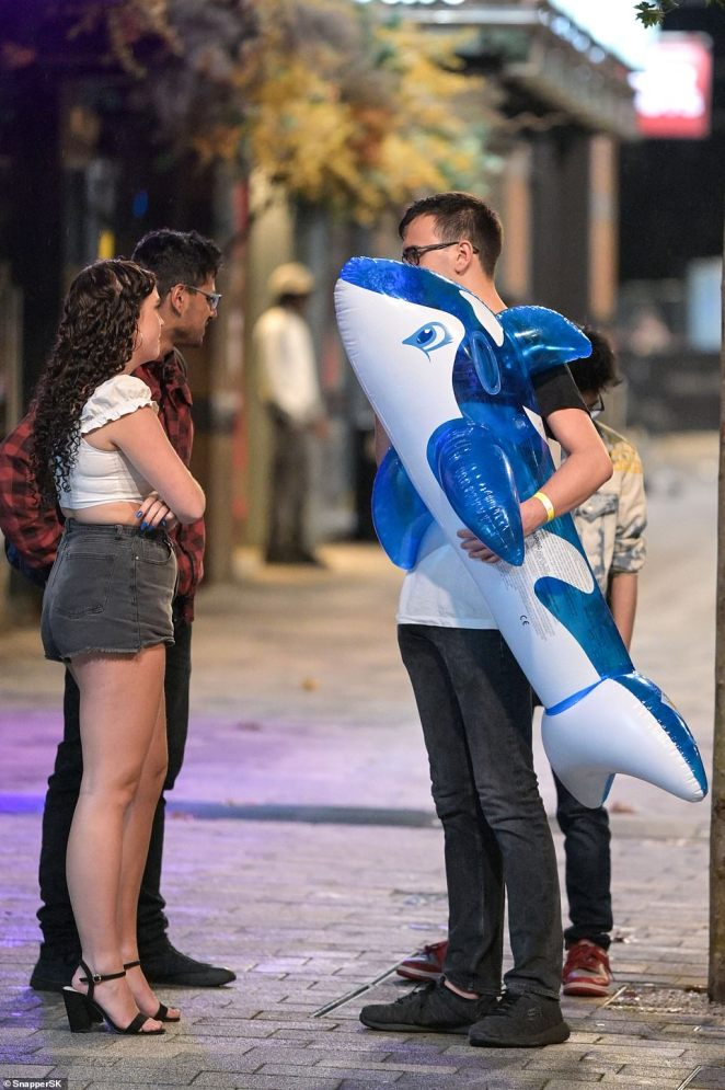 A young man stops to chat with friends while walking an inflatable blue dolphin through the streets of Birmingham
