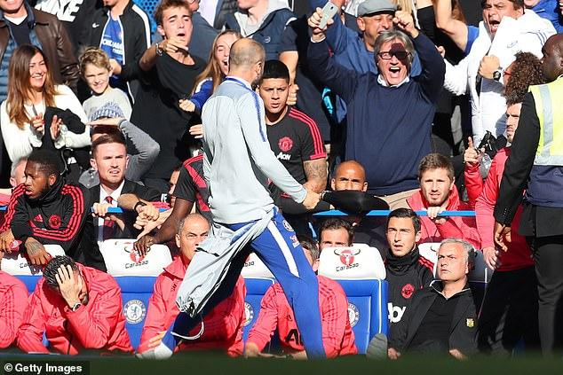 Blues coach Marco Ianni goads towards Mourinho sitting down (right) in the United dugout