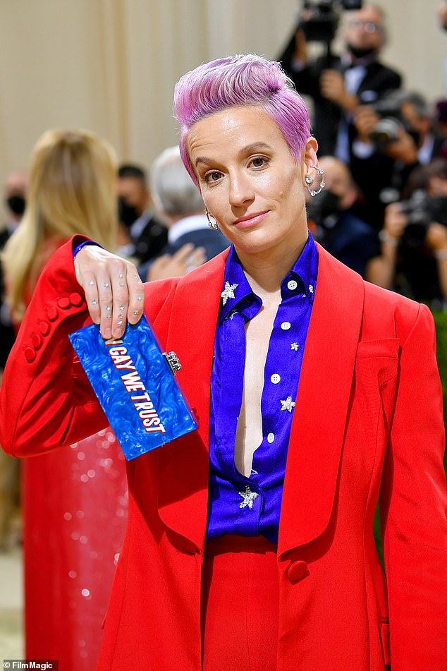 Rapinoe wore a red silk pantsuit with whitea royal blue blouse with white stars emblazoned on it and held a marble blue clutchfeaturing the word 'America' on one side, and 'In Gay We Trust' on the other