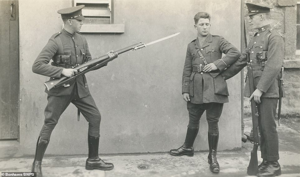 The collection of 200 images belonged to Private Dermot Foley of the Irish Defence Force. The photos show Irish government forces during the civil war of 1922-1923 that followed the Irish War of Independence. One image shows a man with a bayonet pointed at him (above)