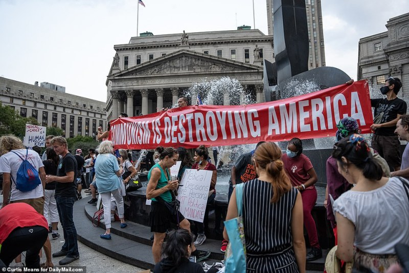 Several rallygoers hold a sign that reads 'Communism is destroying America' in New York's Foley Square on Monday