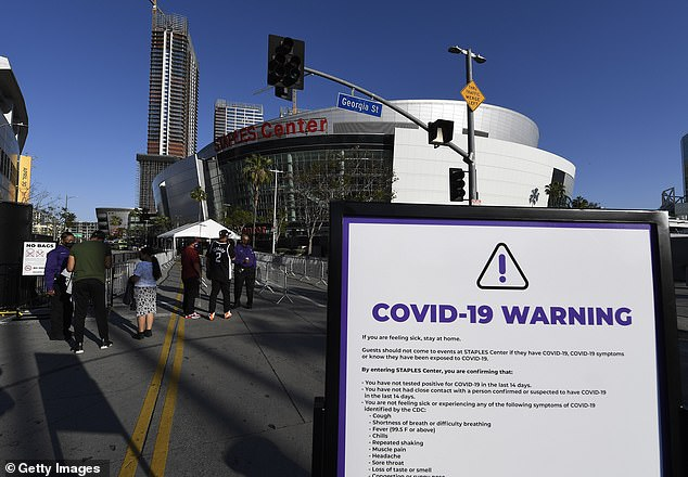 Ushers check the vaccination card or a recent COVID-19 test of arriving fans at Staples Center on April 18, 2021 in Los Angeles, California. It has been over a year since fans have gathered at the Staples Center due to the coronavirus pandemic
