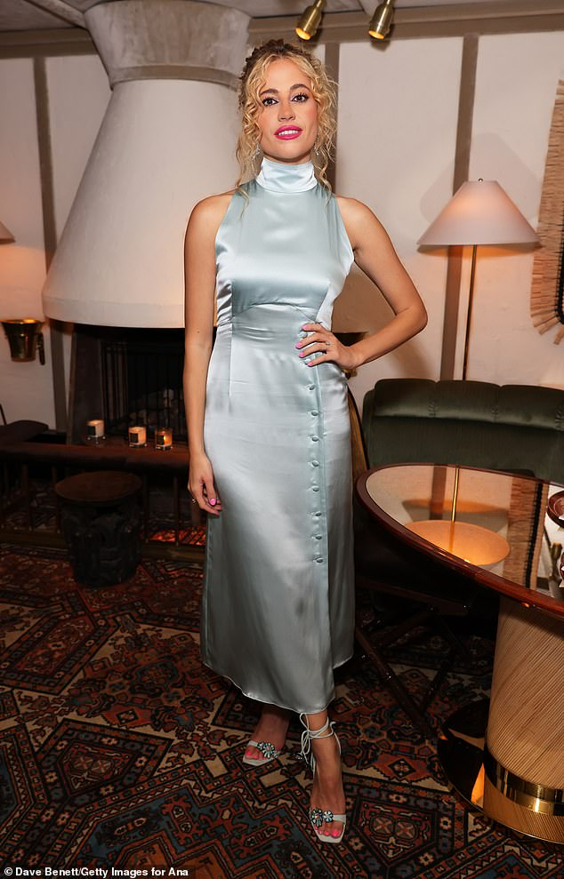 All eyes on her: The pixie lot was all eyes on her as she modeled a silk high-neck frock in Cinderella-blue on Tuesday for the launch of new high-fashion brand Anasim in London.
