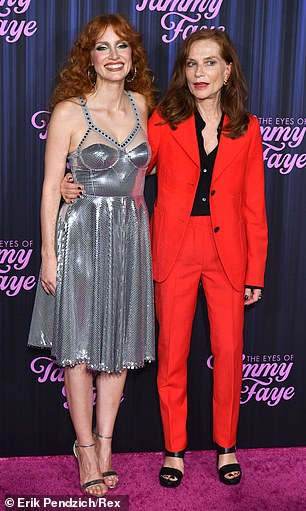 Having a ball: Chastain later met up on the red carpet with French actress Isabelle Huppert, who wowed in a bright red power suit