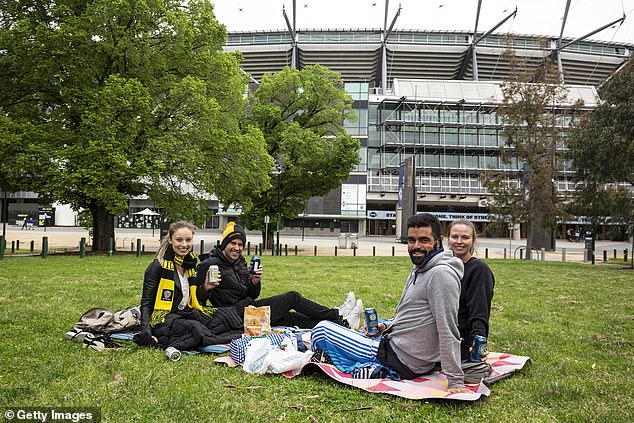 Outdoor picnics will be a possibility for grand final day in Victoria this year, according to health experts (pictured, Tigers fans outside the MCG on grand final day in 2020)