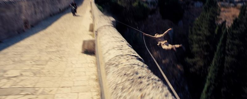 Over the edge!Blood-stained, 007 is seen zooming along the cliff-edge, being shot at, before diving off the side of the wall connected to a rope