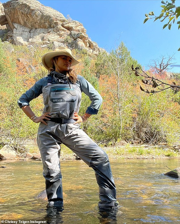 Don't mind me: Chrissy struck a pose in the shallow water after pulling on a pair of waders