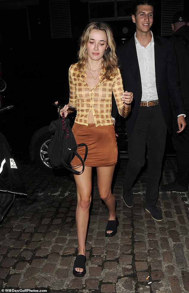 Mystery woman: Meanwhile, the YouTuber's companion put on a leggy display in a thigh-skimming russet-coloured mini skirt and chunky black platform sliders
