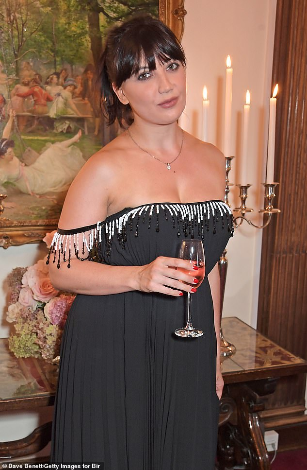 Wow! The model put on a glamorous display in a busty black dress as she beamed for the cameras at the swanky event