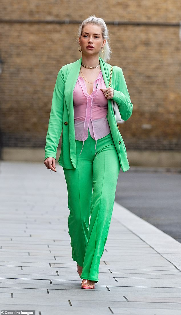 Busty: The model, 23, showcased her curves in the figure-hugging trouser suit and left little to the imagination in the see-through shirt