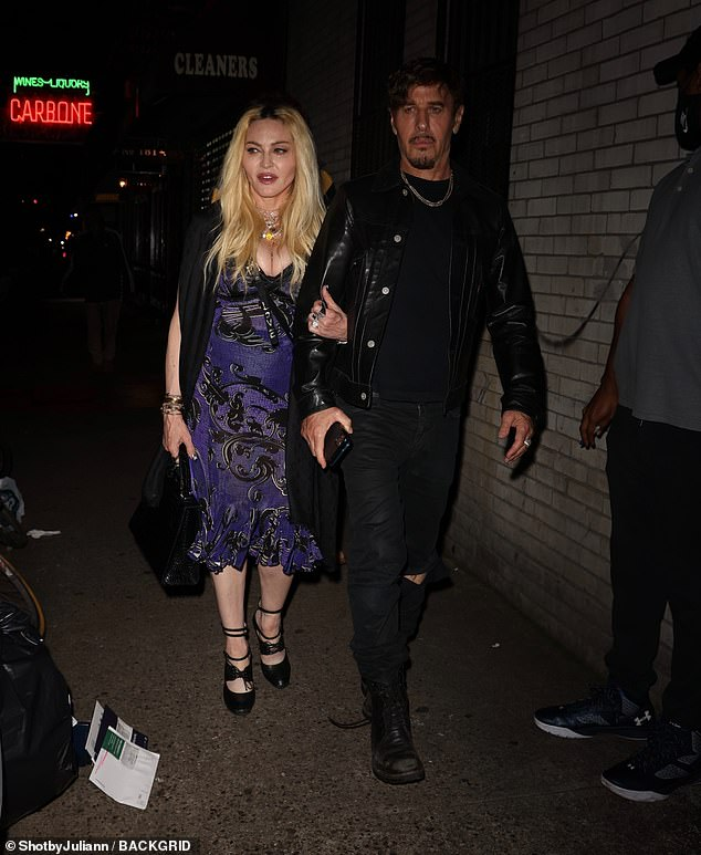 Stepping out:Madonna, 63, wore a blue and black dress teamed with a black cape and stiletto heels as she made her way home from the bash
