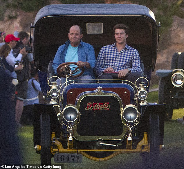 Evans with his father in September 2015. Friends of his told Vanity Fair in 2019 that his parents, hotel magnates, did not like Holmes at first because they 'thought she was a scammer'