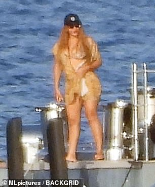 There she is: The R&B legend revealed her curves in a light coloured bikini, worn beneath a delicate sheer wrap as she gingerly climbed aboard the waiting jet-ski
