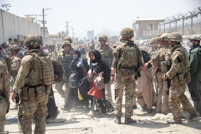 Members of the British and US military are pictured working together on August 20 to help to evacuate people out of Kabul