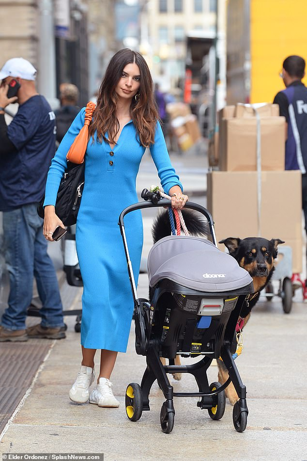 Absolutely gorgeous:The supermodel had a stylish ruched orange handbag slung on one shoulder along with Sly's diaper bag