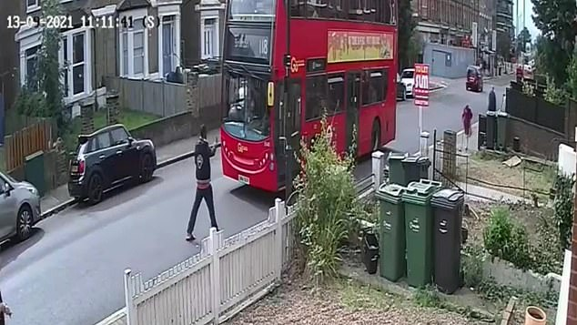 The unidentified man stood in front of the bus blocking its passage through Streatham, south London on Monday morning