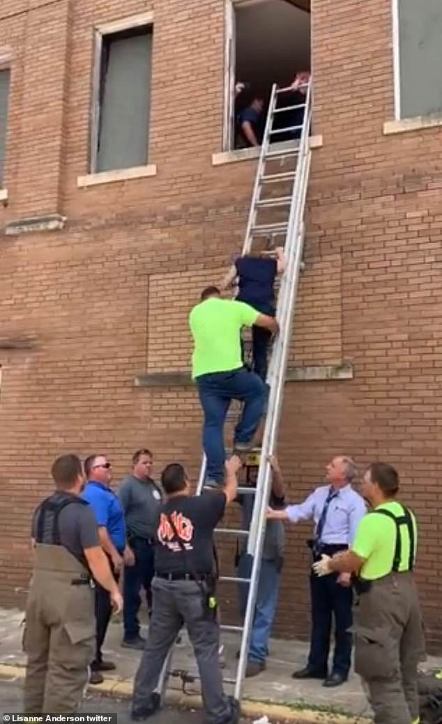 Easy to do: With the help of the team below, McEntire climbed down the ladder and appeared in good spirits despite the traumatic event